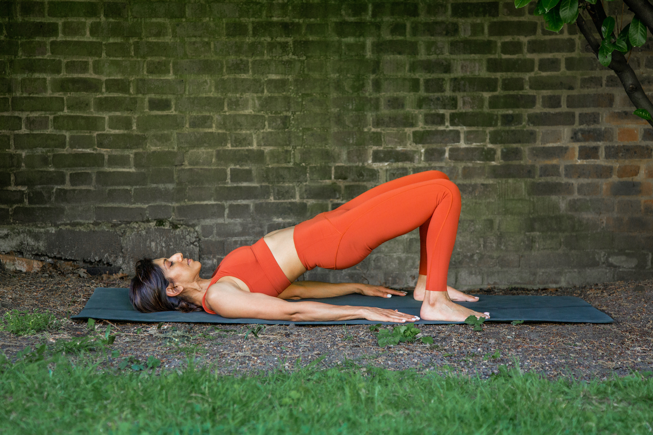 Woman doing a glute bridge with pilates to relieve pain